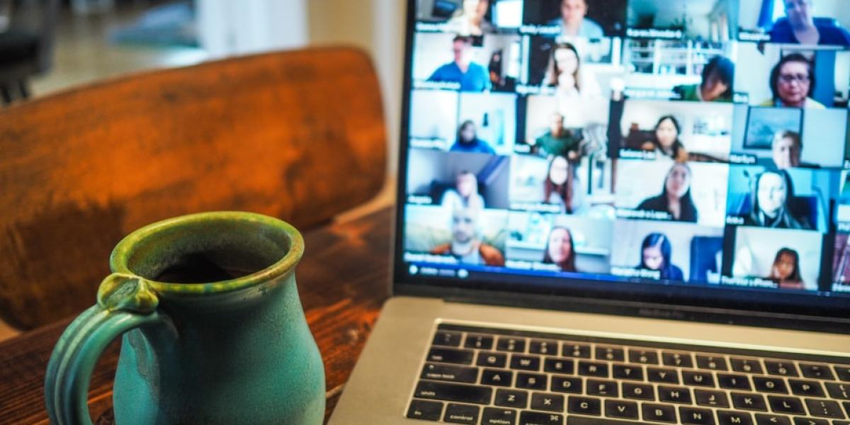 Online meeting: coffee mug by laptop with participants on screen