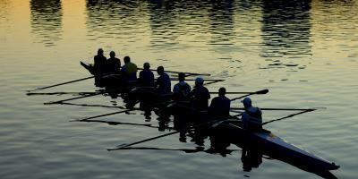 Soutuvene jossa yhdeksän soutajaa hämärässä vesillä. Rowing boat with nine rowers afloat at dusk..