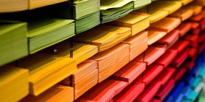 Lokerikko, jossa on vihreitä, keltaisia, punaisia ja sinisiä paperipinoja omissa lokeroissaan.
